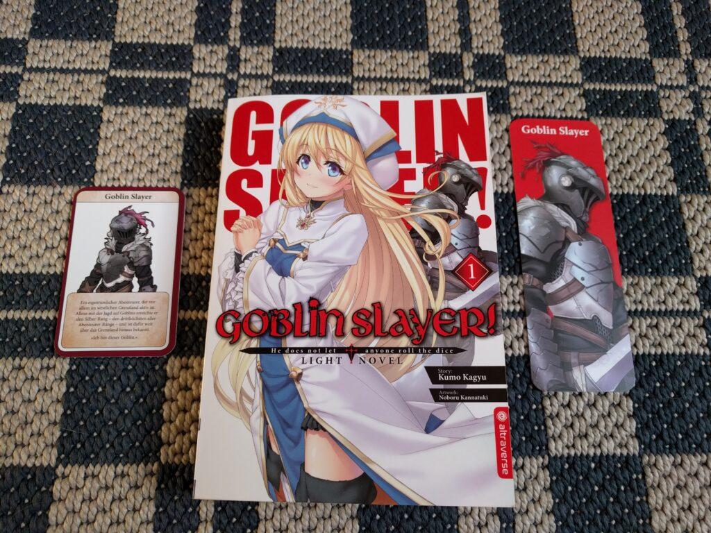 Ein Bild von Band 1 von Goblin Slayer. Rechts davon das Lesezeichen, links davon die Charakter-Karte des Goblin Slayer