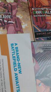 Das Bild zeigt die Beschädigung an Band 05 von SAO Alternative. Das Bild zeigt einen Knick an der oberen Ecke der Rückseite des Buches. So geliefert von Amazon. Nummer 02